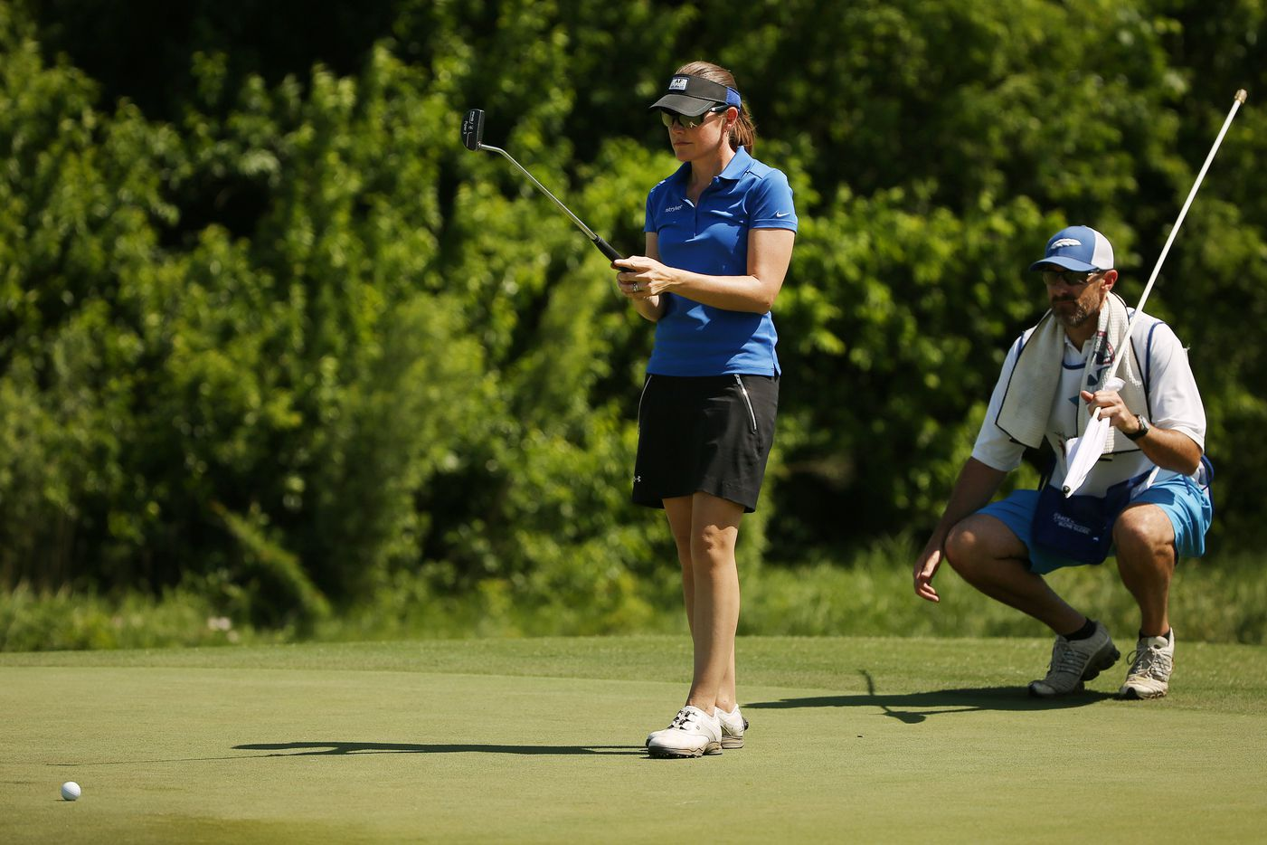 Stephanie Louden, of Frisco, Texas, prepares to putt on the 17th green as her husband, Mike Louden, who is also her caddy, watches on during round one of the 36-hole revised Volunteers of America LPGA North Dallas Classic at the Old American Golf Club in The Colony, Texas Friday May 5, 2018.
