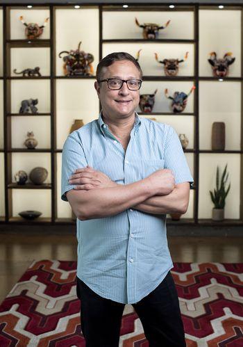 Jorge Baldor, fundador del Mercado369 posa frente a una pared de artesanías hispanas. (Jeffrey McWhorter/Especial para DMN)