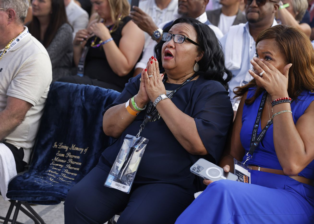 Sandra Pearson Hill (left), sister of Pro Football Hall of Fame inductee Drew Pearson of the Dallas Cowboys, looks skyward next to an empty chair bearing the names of their parents, family members and friends who have passed away. Her oldest daughter Tori Nichole Pearson wipes away a tear as Drew acknowledged them in his acceptance speech during the Class of 2021 enshrinement ceremony at Tom Benson Hall of Fame Stadium in Canton, Ohio, Sunday, August 8, 2021. (Tom Fox/The Dallas Morning News)