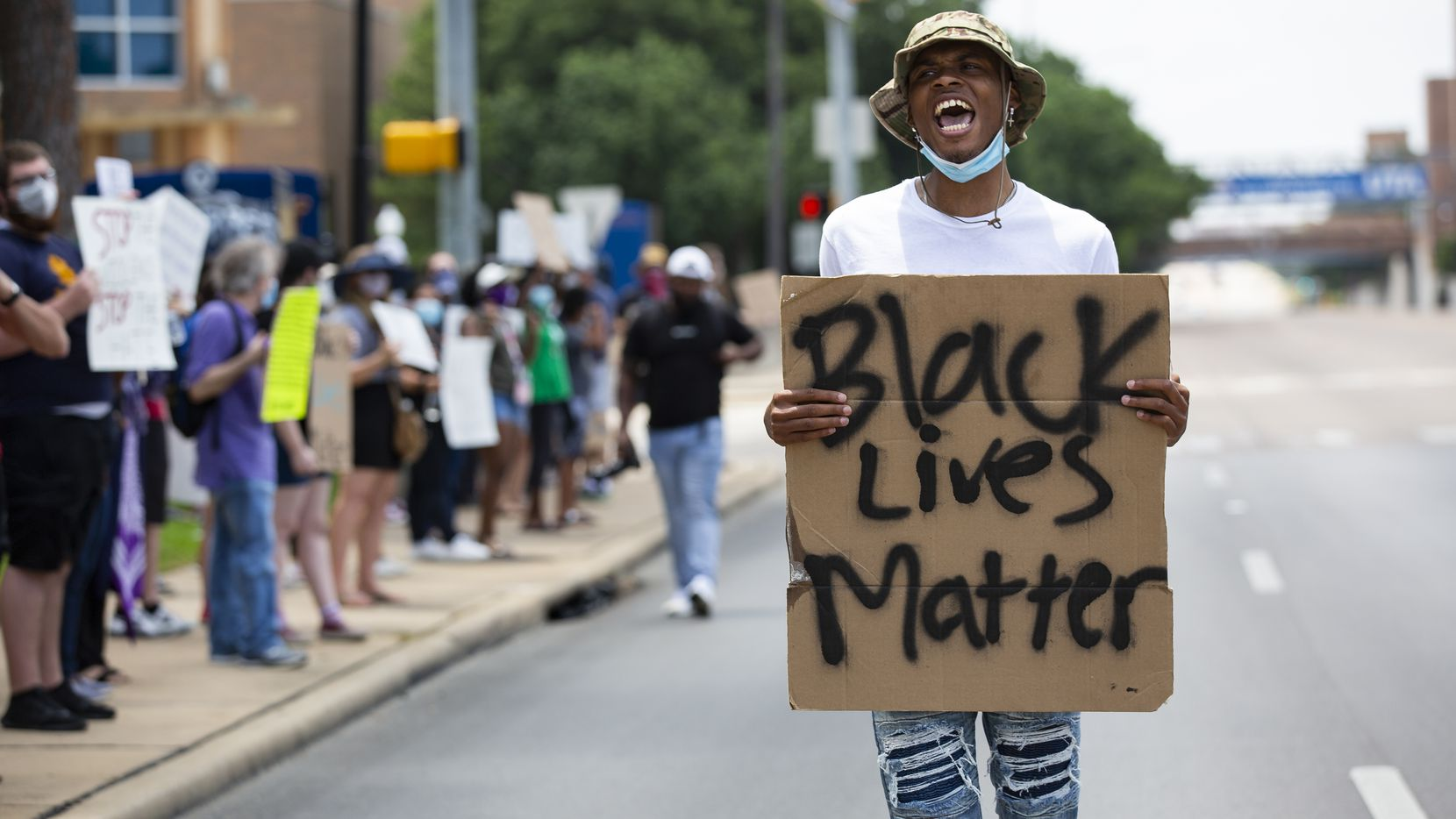 Zyshonne Harris, a senior at UT Arlington, leads the chant as protesters against police brutality line S Cooper St while participating in the School of Social Work's Protest March in Arlington on Monday, June 8, 2020.