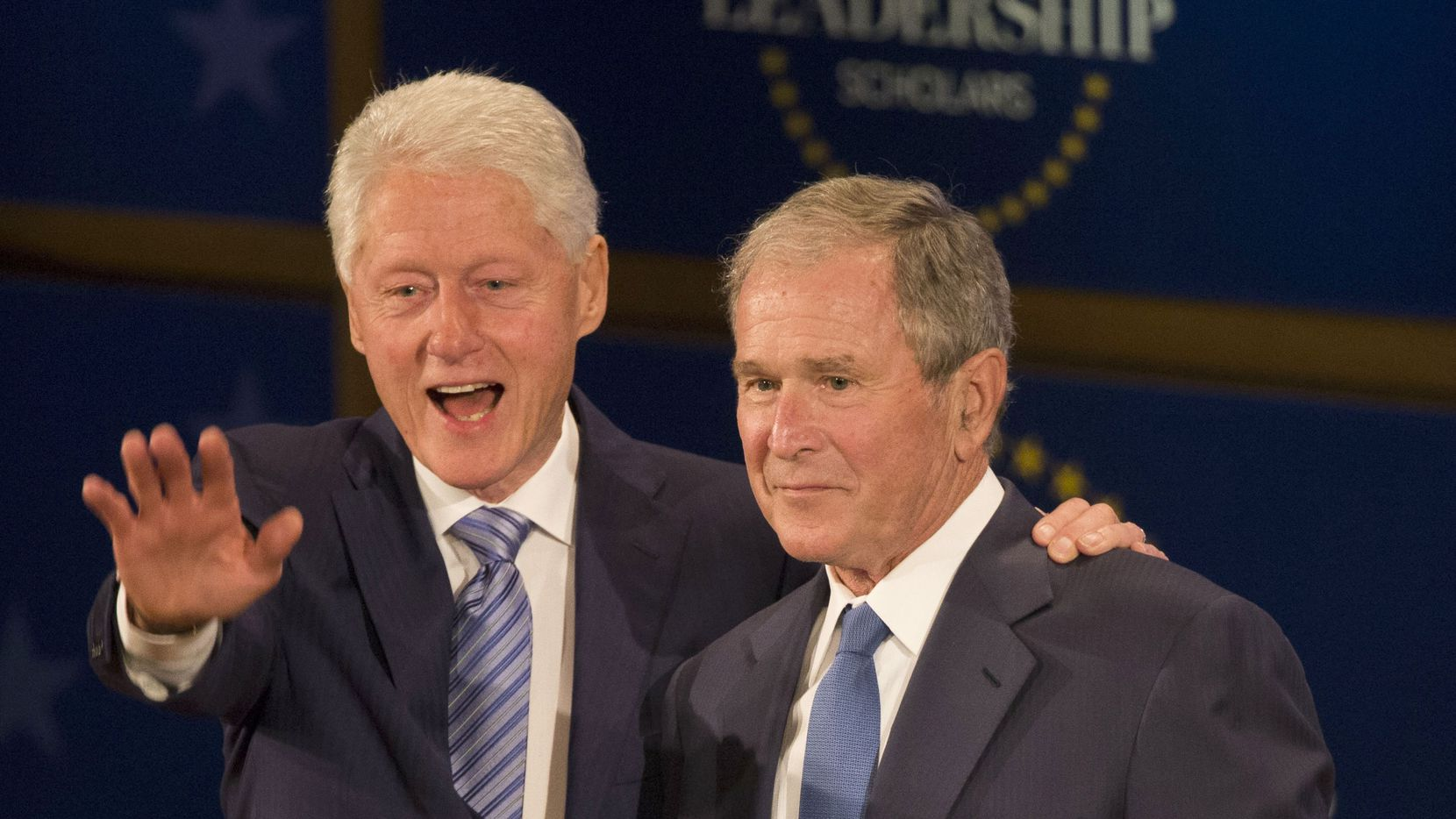 Former Presidents George W. Bush and Bill Clinton wave during the Presidential Leadership Scholars Graduation at the George W. Bush Presidential Center in Dallas.
