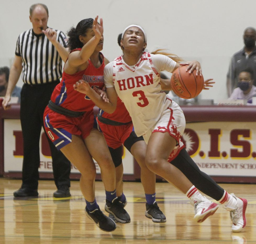Mesquite Horn guard Jasmine Shavers (3) winces as she attempts to drive against the aggressive defense of Duncanville guards Kiyara Howard-Garza (5), left, and Tristen Taylor (11) during first half action. The two teams played their Class 6A area-round playoff basketball game at Loos Field House in Addison on February 23, 2021. (Steve Hamm/ Special Contributor)