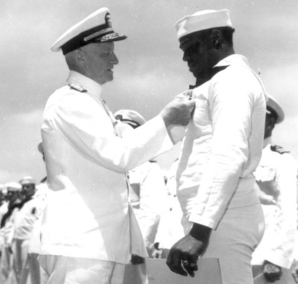 Admiral C. W. Nimitz, the Commander in Chief, Pacific Fleet, pins Navy Cross on Doris Miller, at ceremony on board the USS Enterprise May 27, 1942.