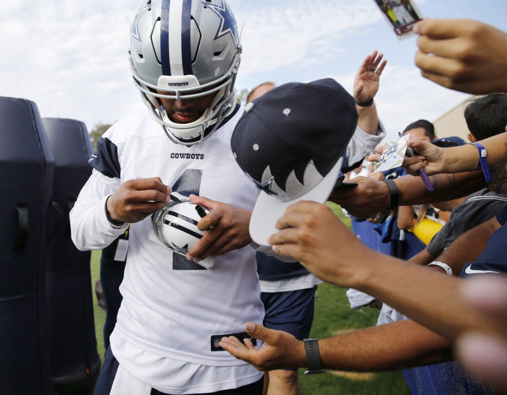 Dallas Cowboys quarterback Dak Prescott (4) signs a helmet after the afternoon practice at training camp in Oxnard, California on Monday, July 24, 2017. (Vernon Bryant/The Dallas Morning News)