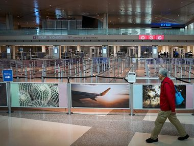 A man wearing a face mask walk past the otherwise empty security lines at Dallas Love Field on Tuesday, April 14, 2020, in Dallas.  (Smiley N. Pool/The Dallas Morning News)