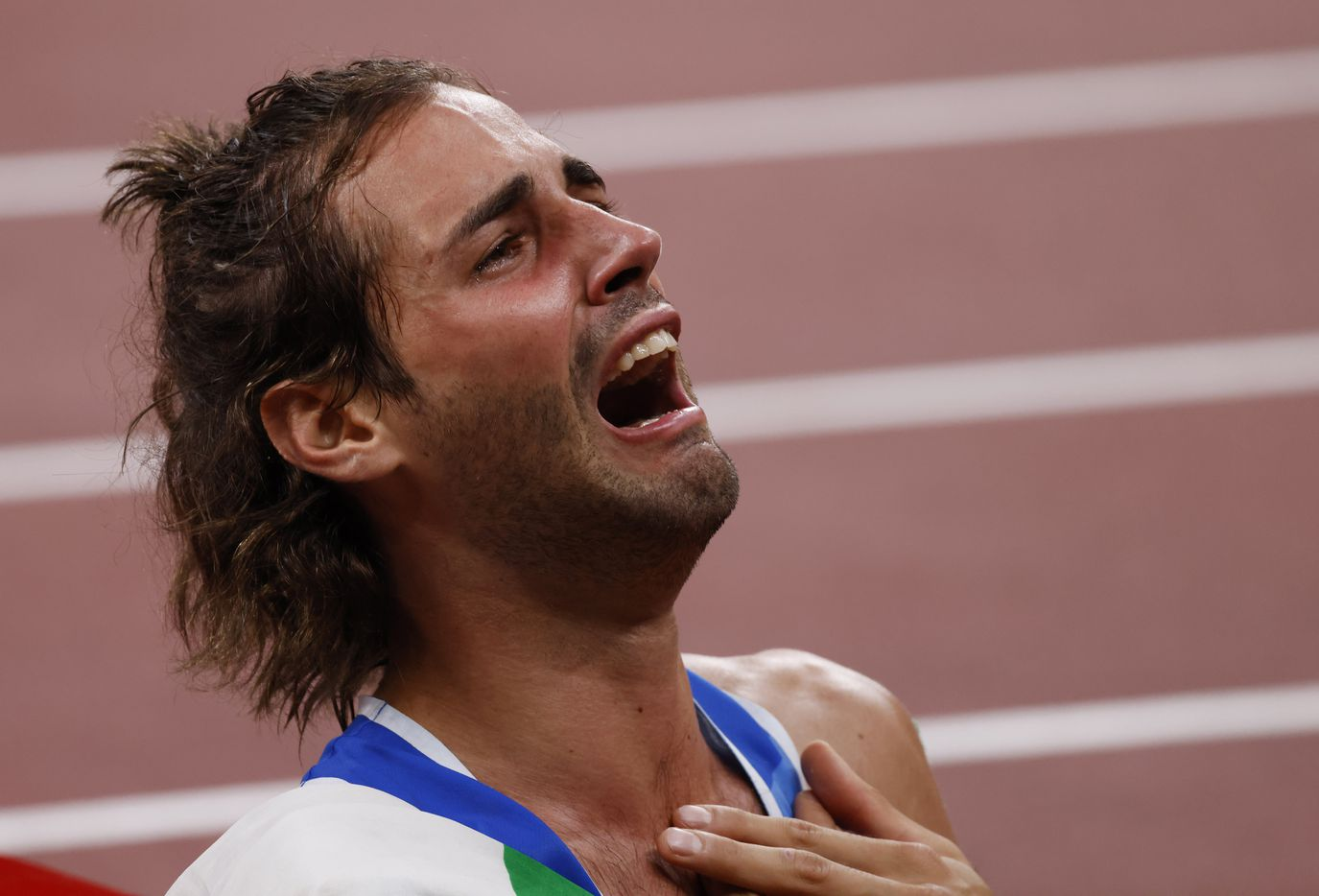 Italy's Gianmarco Tamberi gets emotional after winning a gold medal in the men's high jump final during the postponed 2020 Tokyo Olympics at Olympic Stadium, on Sunday, August 1, 2021, in Tokyo, Japan. Tamberi will share a gold medal with Qatar's Mutaz Essa Barshim who also cleared 2.37 meters in the final. (Vernon Bryant/The Dallas Morning News)