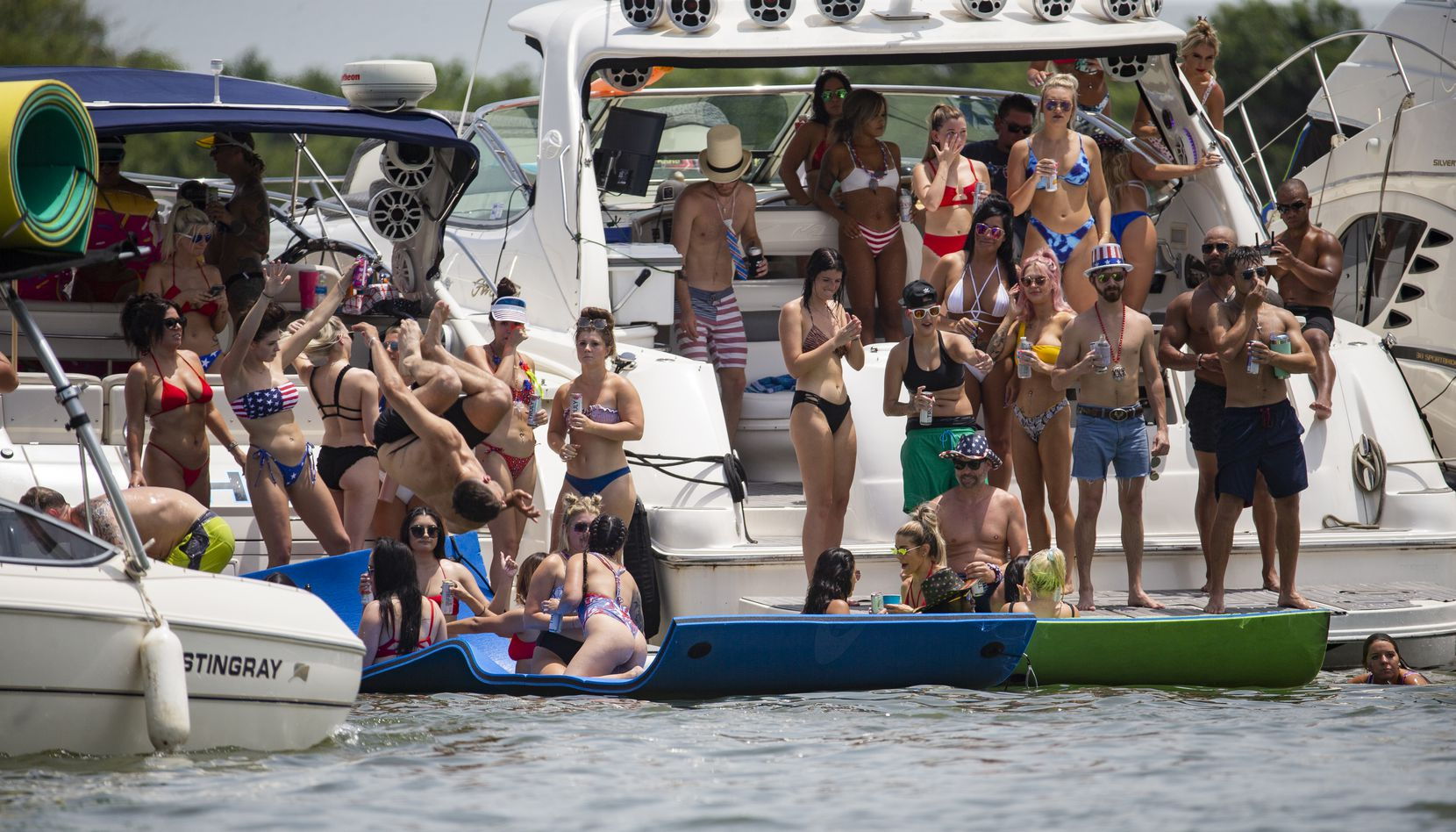 Partiers gathered en masse and without masks for Fourth of July fun under the sun at Lewisville Lake's Party Cove on Saturday.