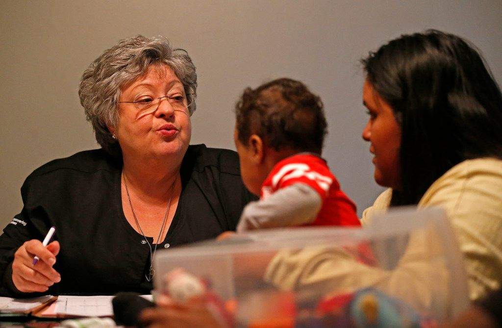 Suzanne Borman (left), a registered nurse with the WiNGS and Nurse-Family Partnership Program, asks her client Genesis Cruz (right) about 10-month-old baby Jayden Griffin while visiting Cruz's home in Mesquite.