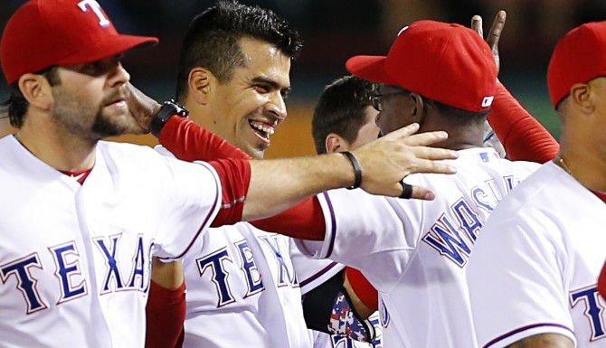 Robinson Chirinos (centro) recibe un abrazo del entonces mánager de Texas, Ron Washington, en un juego en el  Globe Life Park de Arlington en abril del 2014. Washinton fue piloto de los Rangers por más de ocho años. (Staff Photographer/TOM FOX)