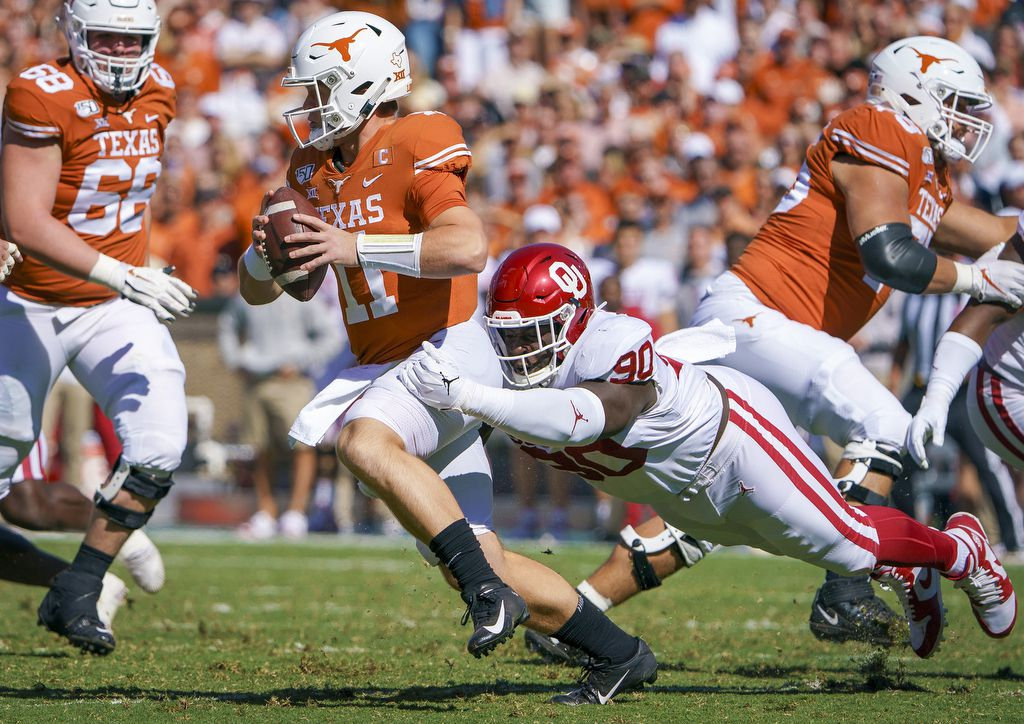 Texas quarterback Sam Ehlinger (11) is sacked by Oklahoma defensive lineman Neville Gallimore (90) during the first half of an NCAA football game at the Cotton Bowl on Saturday, Oct. 12, 2019, in Dallas.