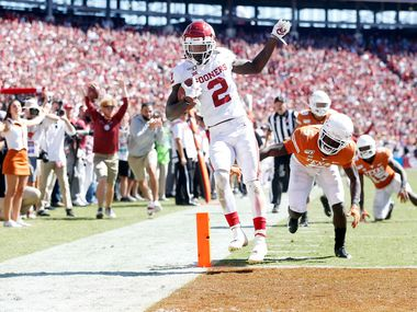 FILE - Oklahoma wide receiver CeeDee Lamb (2) beats Texas defensive back D'Shawn Jamison (5) for a touchdown in the second half of the Red River Showdown at the Cotton Bowl in Dallas on Saturday, Oct. 12, 2019.