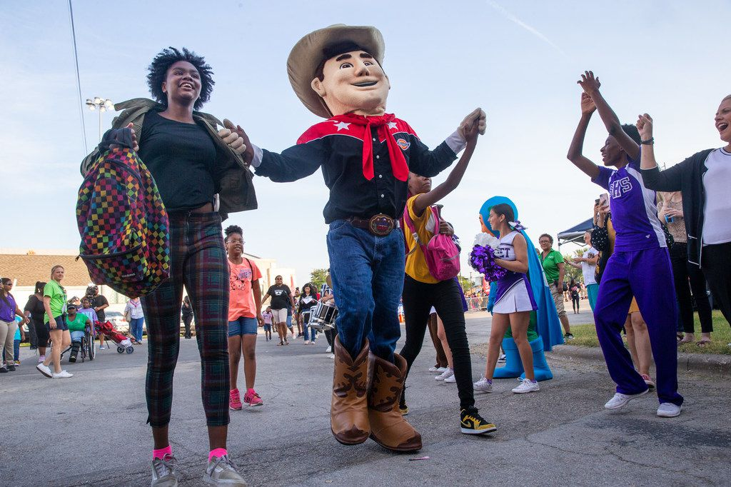 Samaria Jackson, 15 (left), skips into the 23rd annual Mayor's Back to School Fair at the Fair Park Centennial Hall in Dallas on Friday, Aug. 2, 2019. Jackson was the first in line, and had been there since 2 a.m., she said. Thousands of children and their family members were expected to attend, and the event included health and eye screenings, dental screenings, backpack giveaways and more.