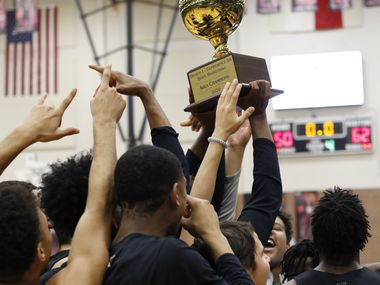 Members of the Waxahachie Indians celebrate with their Class 6A Region 1 Area Champions trophy following their 62-50 victory over Coppell to advance. The two teams played their Class 6A area-round boys basketball playoff game at Mansfield Timberview High School in Arlington on February 28, 2020.