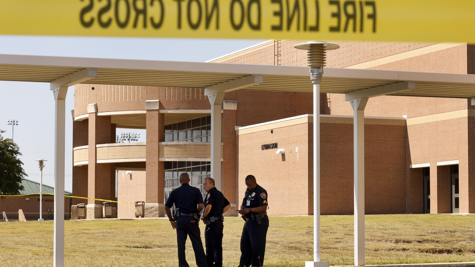 Mansfield ISD police officers secure the door where most of the activity took place following a shooting inside Mansfield Timberview High School in Arlington, Texas, Wednesday, October 6, 2021. Four people were injured in the shooting and the suspect turned himself into the Arlington police.