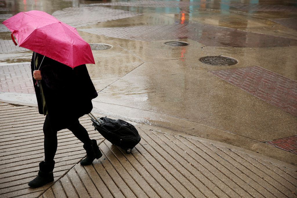 In this Nov. 8 file photo, rain falls on a pedestrian crossing Main and South St. Paul streets in downtown Dallas
