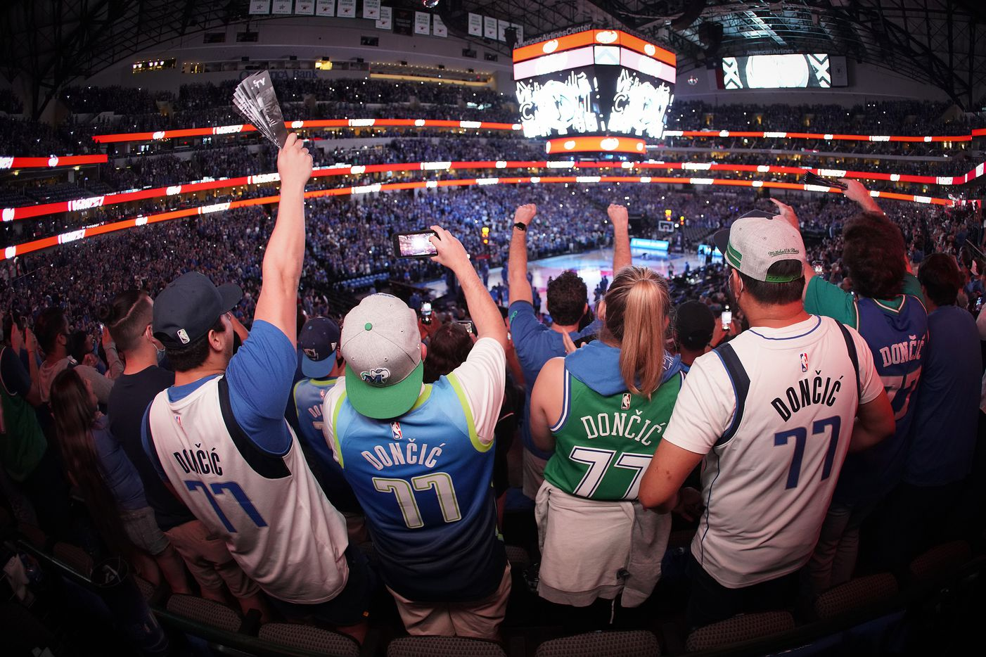 Dallas Mavericks fans, all wearing guard Luka Doncic #77 jerseys, cheer as their team takes the court before an NBA playoff basketball game against the LA Clippers at American Airlines Center on Friday, May 28, 2021, in Dallas.  (Smiley N. Pool/The Dallas Morning News)