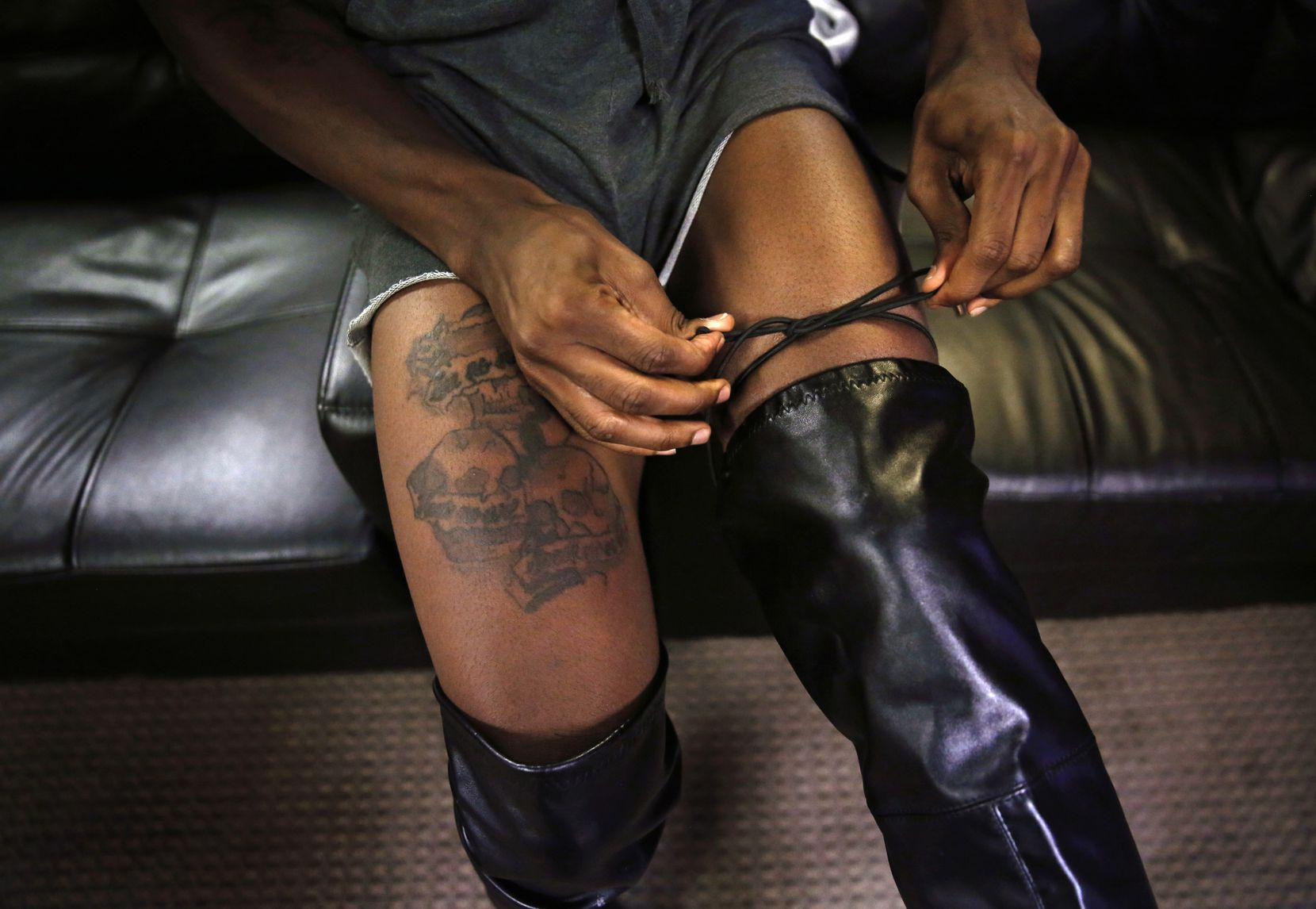 Andrew Williams ties up knee-high boots before a voguing practice at United Black Ellument in Dallas on Friday, Aug. 10, 2018.