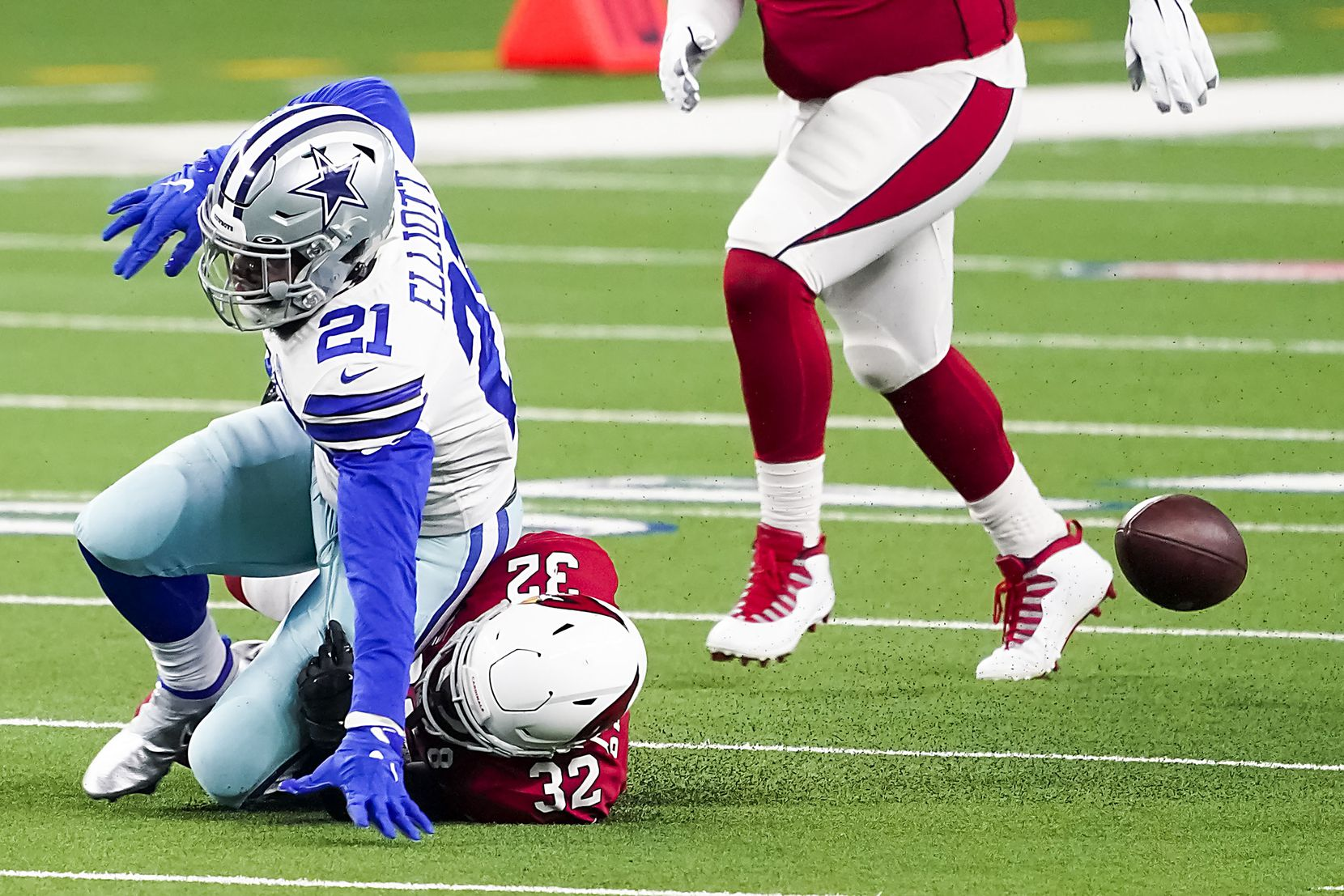 Dallas Cowboys running back Ezekiel Elliott (21) fumbles on a hit from Arizona Cardinals strong safety Budda Baker (32) during the first quarter of an NFL football game at AT&T Stadium on Monday, Oct. 19, 2020, in Arlington. The Cardinals recovered the fumble. (Smiley N. Pool/The Dallas Morning News)