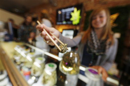 In this Friday, Dec. 18, 2015, photograph, LivWell store manager Carlyssa Scanlon shows off some of the products available in the marijuana line marketed by rapper Snoop Dogg in one of the marijuana chain's outlets south of downtown Denver. LivWell grows the Snoop pot alongside many other strains on its menu.