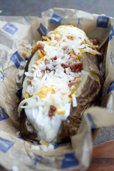 NOT THAT: A loaded baked potato at the ballpark has 450 calories and 26 grams of fat. To make the baked potato a more nutritious option, ditch the sour cream and cheese. The bacon bits can be a smart splurge, with only 5 calories per tablespoon.