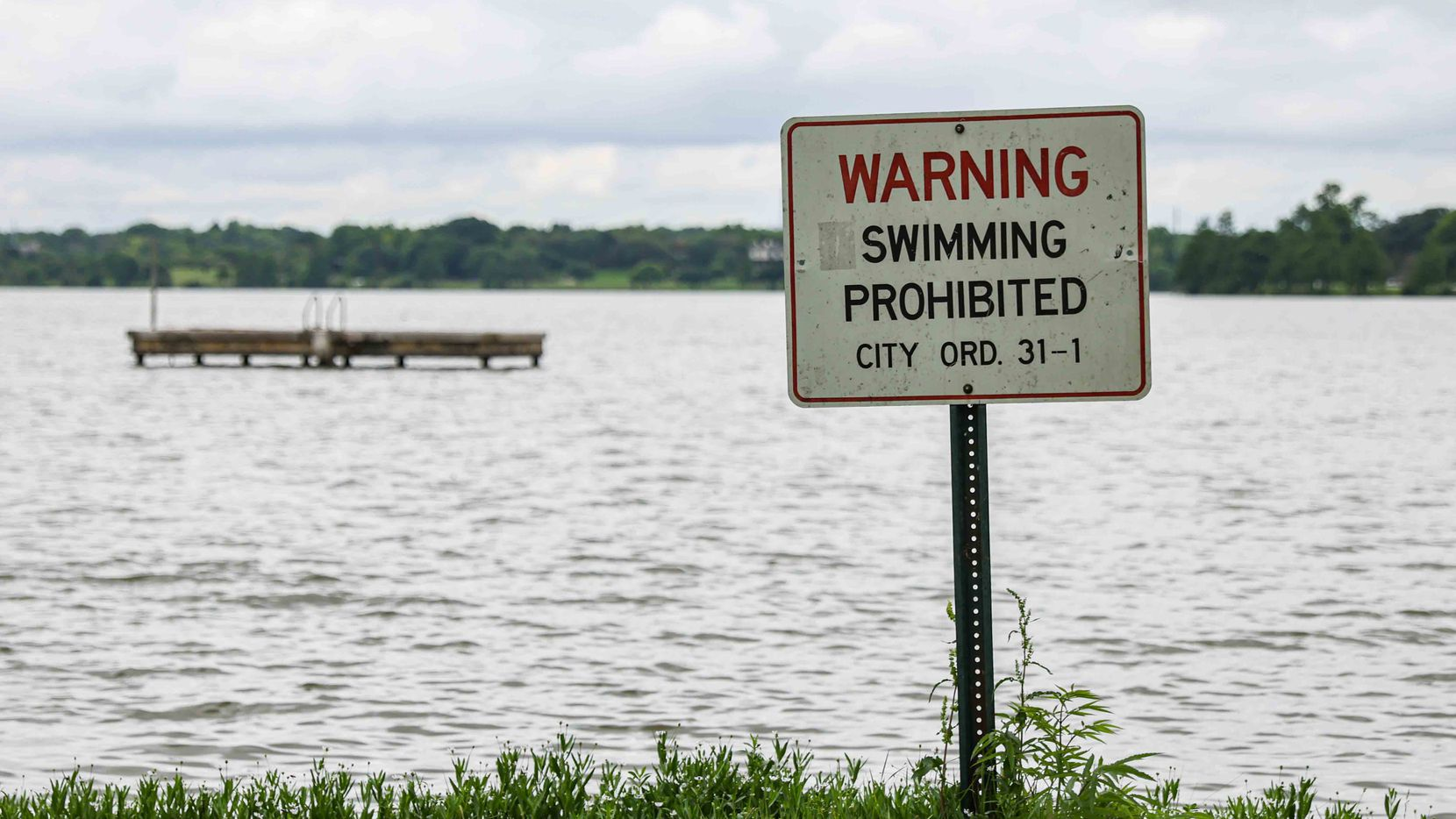A sign near the Bath House Cultural Center on the east shore of White Rock Lake in Dallas notes the city's' ban on swimming at the lake.