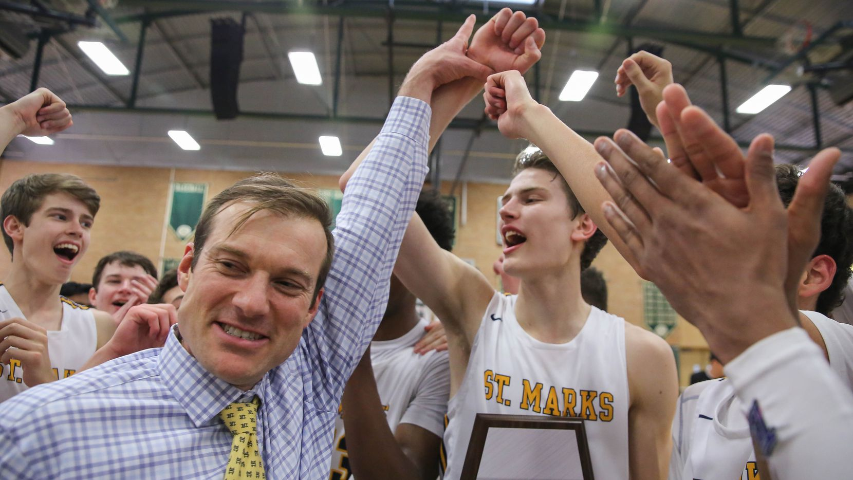 St. Mark's coach Greg Guiler (left) celebrates with his team after winning a SPC boys basketball championship game against Houston Christian on Feb. 15, 2020 held at The Greenhill School inAddison. St. Mark's won 85-57.