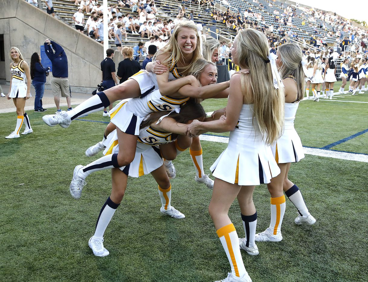 Highland Park High School cheerleader Elle Barrett (top) falls when the cheer squad tried to stack girls up before kickoff as Highland Park High School hosted Rockwall High School at Highlander Stadium in Dallas on, Friday, September 17, 2021. (Stewart F. House/Special Contributor)