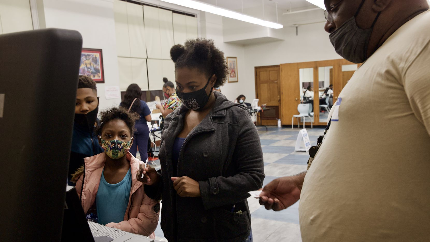 Krystal White (center) casts a ballot in the general election as her children Perell (left) and Keyelle (second from left), 9, and election clerk Darrell Brown, look on at James Madison High School in South Dallas on Election Day on Nov. 3, 2020.