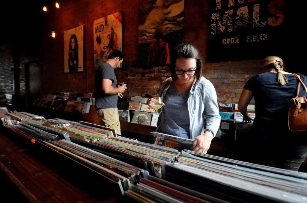 Amy McCleary browses through records with a drink in hand at Off The Record in Deep Ellum, TX on September 7, 2014.