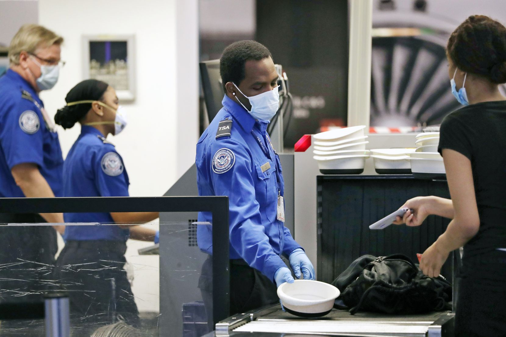 TSA officers wear protective masks at a security screening area at Seattle-Tacoma International Airport Monday, May 18, 2020, in SeaTac, Wash. Monday was the first day that travelers at the airport were required to wear face coverings in the public areas there. The Port of Seattle has encouraged its employees to wear face coverings, and all federal agencies that operate at the airport require their employees to wear face coverings. All airlines operating at SeaTac require employees and passengers to wear face coverings. (AP Photo/Elaine Thompson)