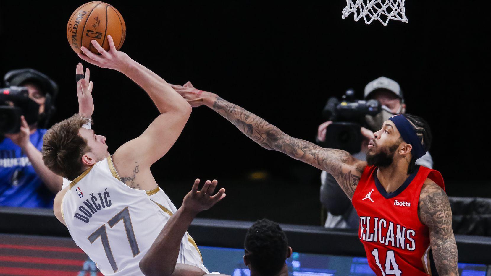 Dallas Mavericks guard Luka Doncic (77) attempts a shot as New Orleans Pelicans forward Brandon Ingram (14) defends during an NBA basketball game in Dallas, Friday, February 12, 2021. Dallas won 143-130.