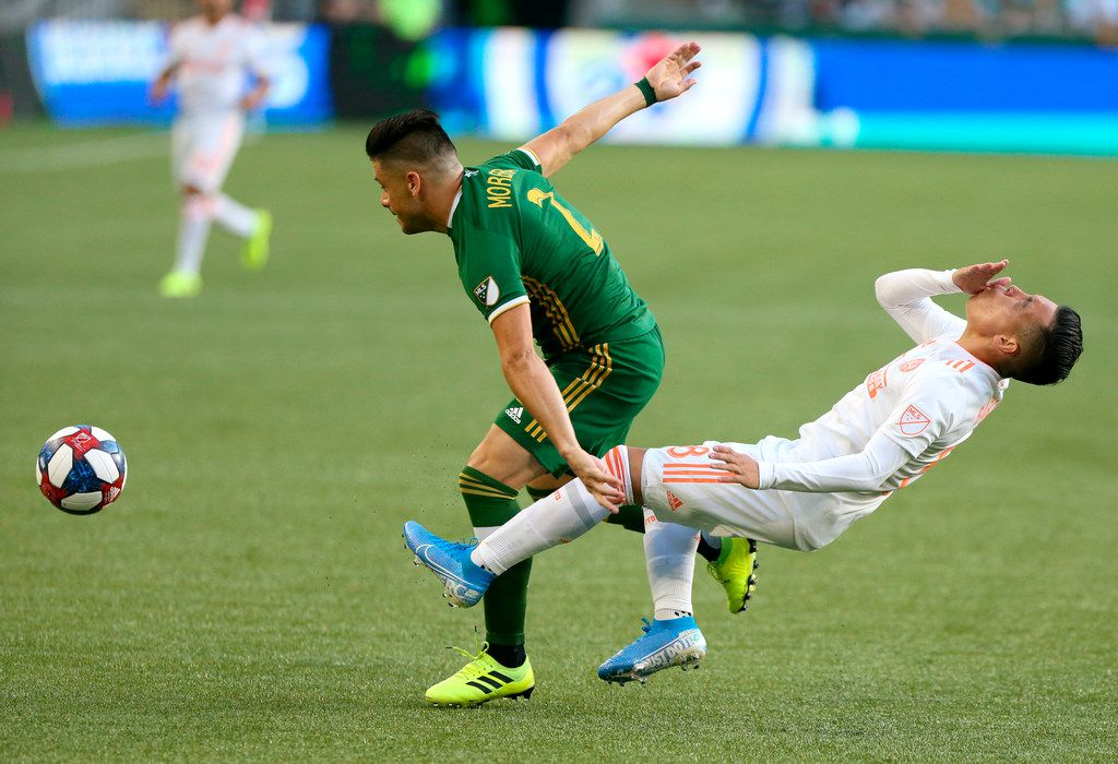 Atlanta United's Ezequiel Barco, right, is fouled by Portland Timbers' Jorge Moreia during an MLS soccer match in Portland, Ore., on Sunday, Aug. 18, 2019. (Sean Meagher/The Oregonian via AP)