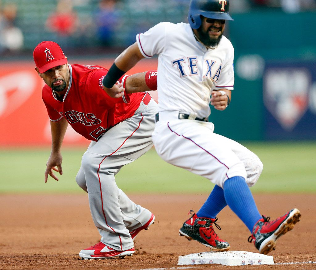 Texas Rangers second baseman Rougned Odor (12) pulls up with a leg injury before getting back to first base during the first inning against Los Angeles Angels first baseman Albert Pujols (5) at Globe Life Park in Arlington, Monday, April 9, 2018. Odor was trying to get back to first on a fly out by Elvis Andrus to right. Odor left the game and was replaced by Jurickson Profar (19). (Tom Fox/The Dallas Morning News)