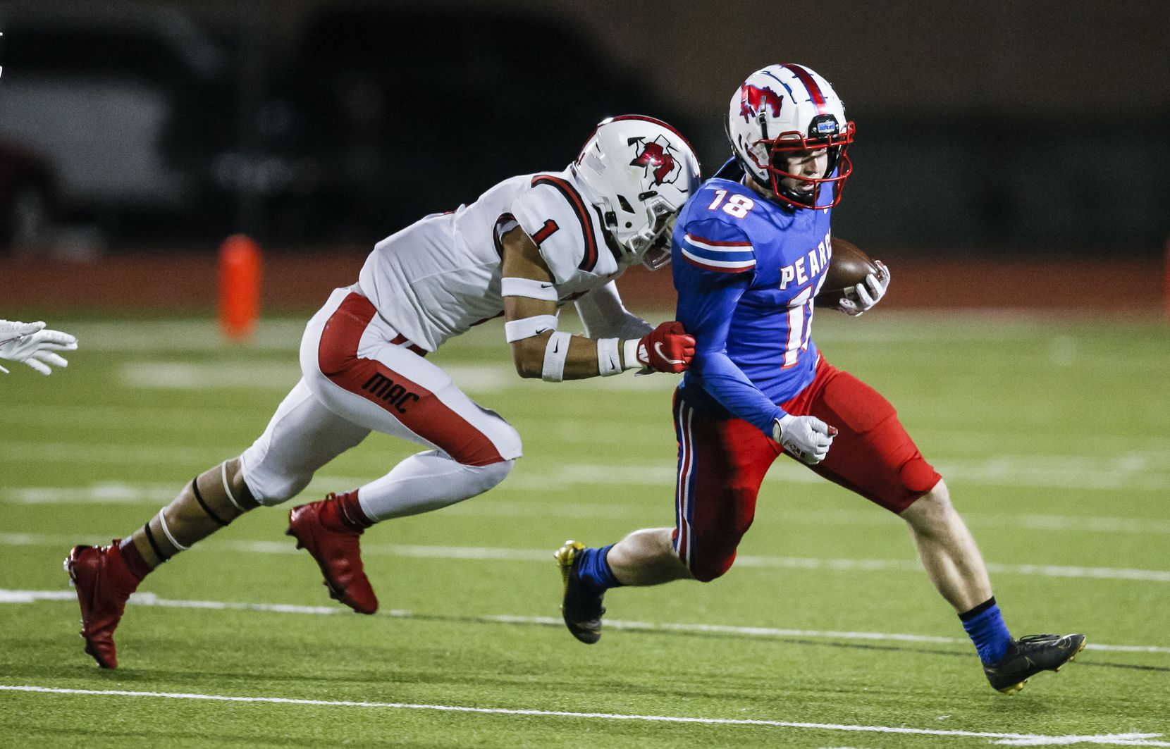 Irving MacArthur senior Roland Jackson (1) tackles JJ Pearce junior running back Adam Velin (18) during the first half of a high school playoff football game at Eagle-Mustang Stadium in Richardson, Thursday, December 3, 2020. (Brandon Wade/Special Contributor)