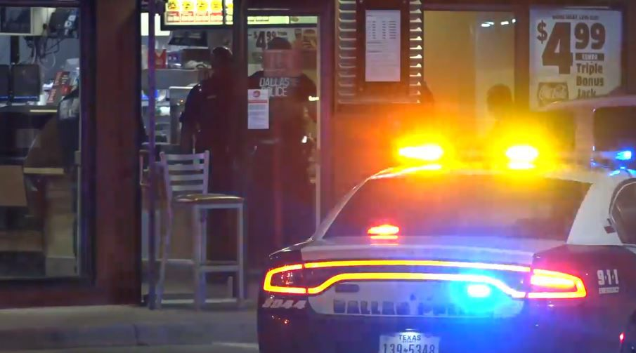 Dallas police officers investigate a shooting that left one employee wounded Wednesday morning at a Jack In The Box in southeast Oak Cliff.