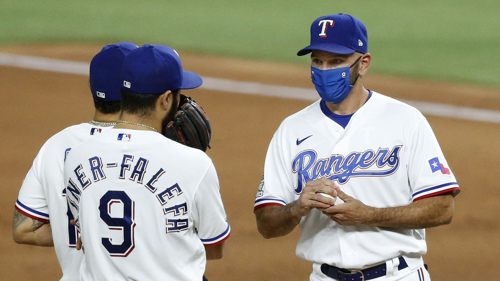 Texas Rangers manager Chris Woodward (right) visits with shortstop Isiah Kiner-Falefa (9) on the mound after pulling relief pitcher Juan Nicasio (40) during the eighth inning at Globe Life Field in Arlington, Monday, August 17, 2020. Woodward was suspended by the league for a game. Nicasio gave up a grand slam to San Diego Padres Fernando Tatis Jr.
