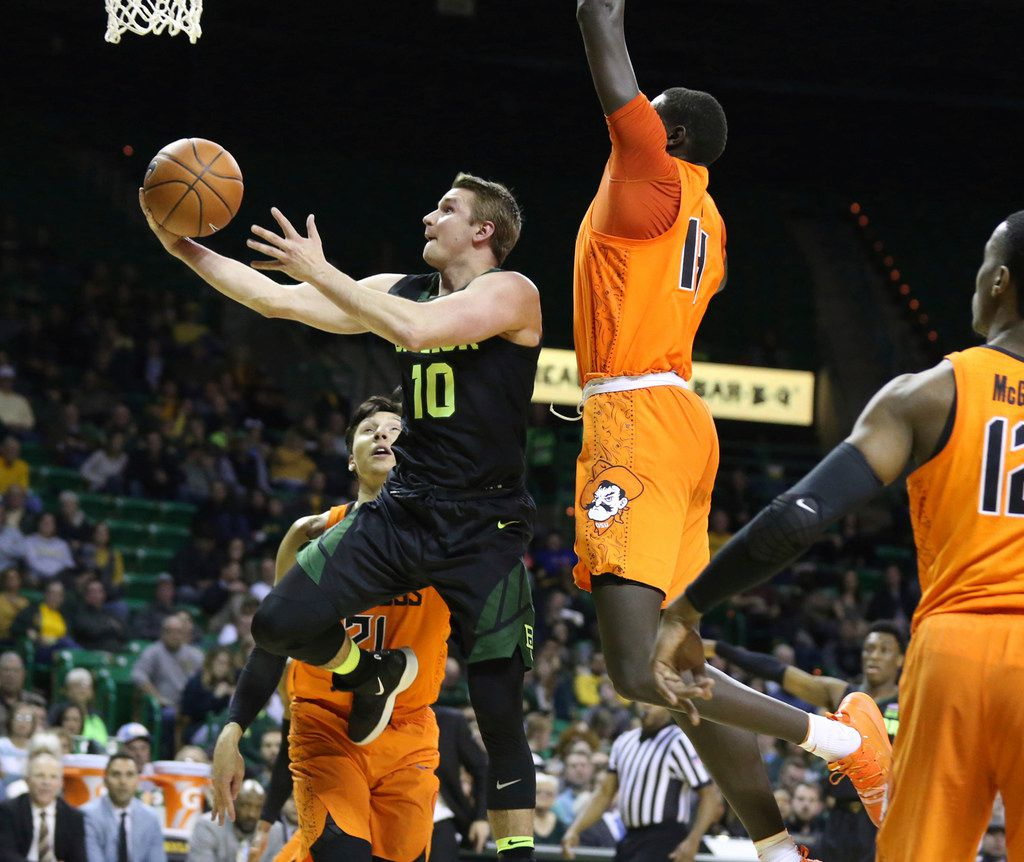 FILE - Baylor guard Makai Mason, left, drives and scores past Oklahoma State forward Yor Anei, center-right, during the second half of a game on March 6, 2019, in Waco. (Rod Aydelotte/Waco Tribune Herald via AP)