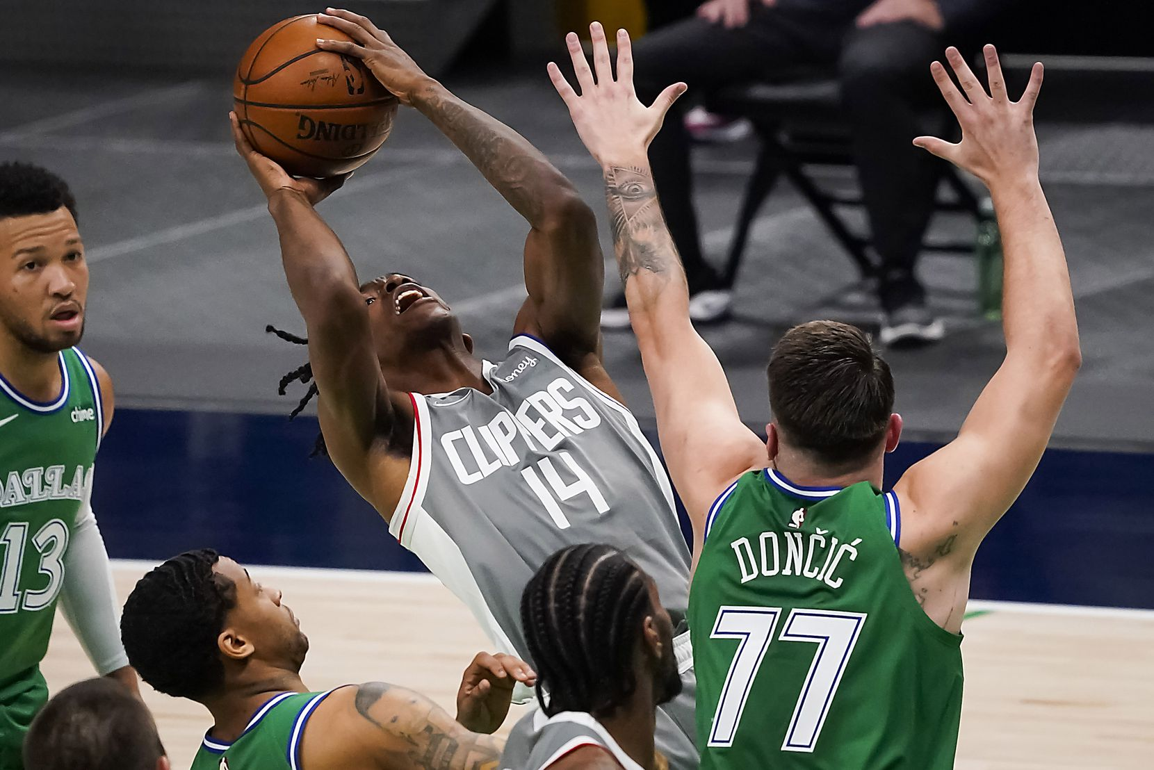 LA Clippers guard Terance Mann (14) is defended by Dallas Mavericks guard Luka Doncic (77) during the first quarter of an NBA basketball game at American Airlines Center on Wednesday, March 17, 2021, in Dallas.