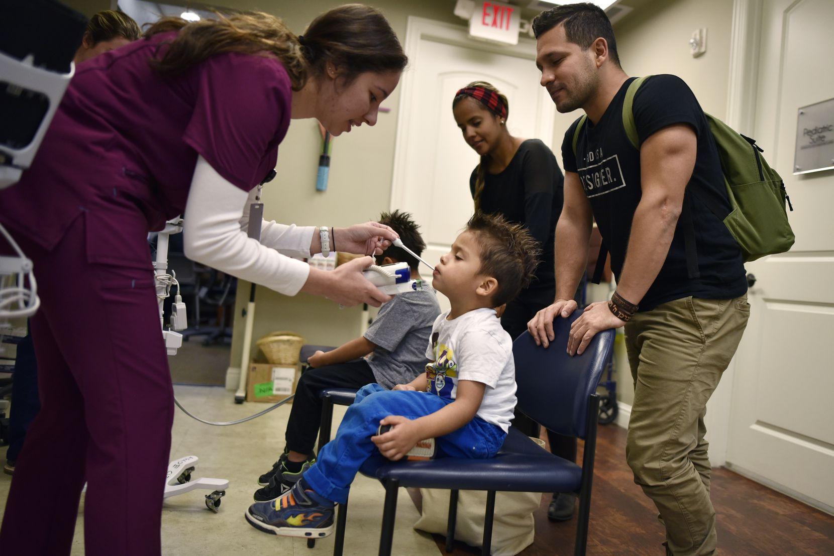 Nursing student Stephanie Beaton (left) checks the temperature of Matias Bonilla, 3, while his father, Jhonatan Bonilla, looks on at Agape Clinic in Dallas. With them is Sandra Duarte, the children's mother.