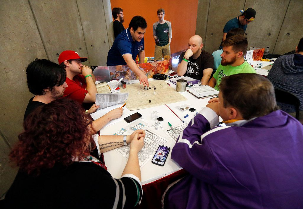 People gathered around a game table to play Dungeons and Dragons.