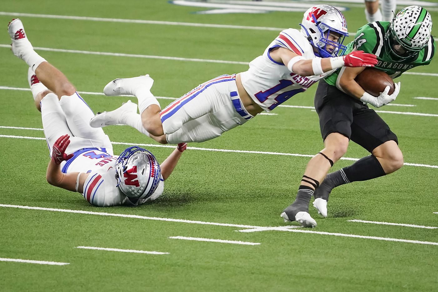Southlake Carroll wide receiver Brady Boyd (14) breaks the tackles of both Austin Westlake defensive backs Michael Taaffe (14) and Jax Crockett (4) on a 49-yard touchdown play during the first quarter of the Class 6A Division I state football championship game at AT&T Stadium on Saturday, Jan. 16, 2021, in Arlington, Texas.