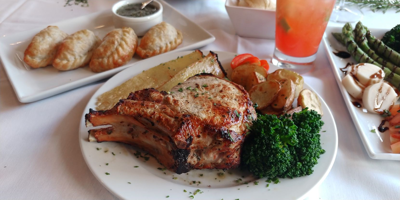 12 Cuts Brazilian Steakhouse's four-course holiday takeout menu that serves three people includes grilled bone-in pork chops, grilled pineapple, broccolini, mashed potatoes, beef empanadas, cheese bread, chimichurri and a choice of chocolate cake or flan.