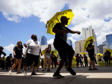 Relius Johnson dances while carrying one of 239 umbrellas distributed with the names of people killed by police or racial  violence during a rally commemorating Juneteenth at Dallas City Hall on Friday, June 19, 2020.