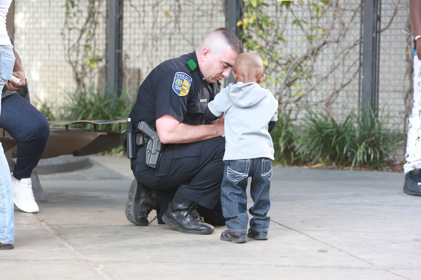 DART Officer Elmar Cannon interacts with a boy during a patrol in 2015 near the West End district in downtown Dallas.