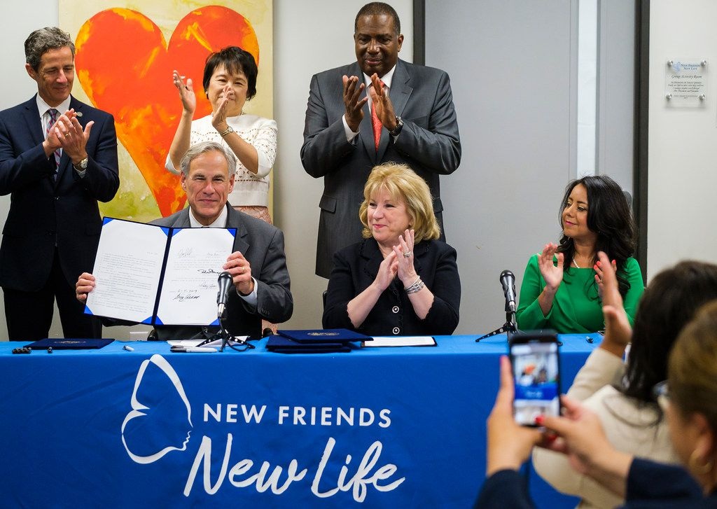 Governor Greg Abbott holds up House Bill 1590 after signing the legislation during a bill signing ceremony at New Friends New Life on Tuesday, June 4, 2019, in Dallas. With the him are (from left) Sen. Kelly Hancock, Rep. Angie Chen Button, Sen. Royce West, Sen. Jane Nelson and Rep. Victoria Neave.