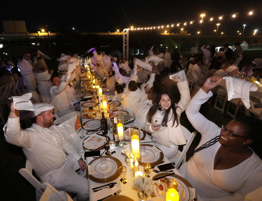 Guests twirl their napkins during a secret Diner en Blanc event at Reunion Park in Dallas on Nov. 9, 2018.