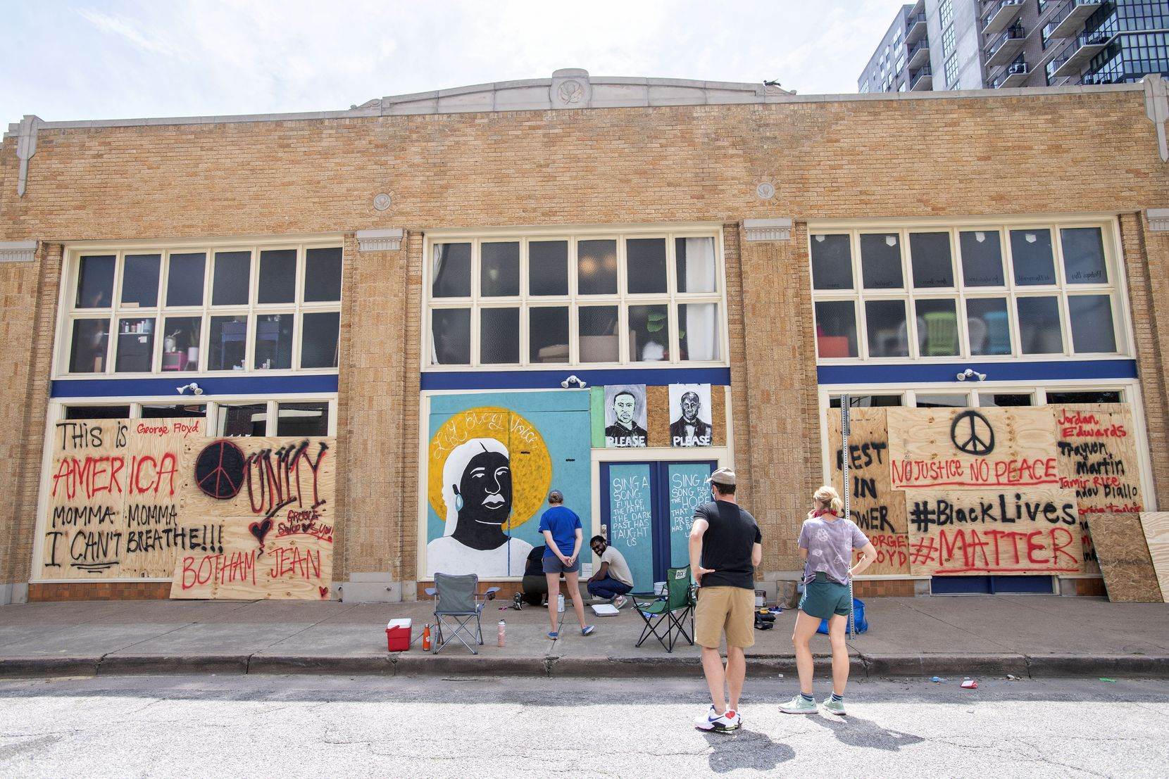 Friends watch Desiree Vaniecia and Joeneal Berry paint a mural on plywood on Monday, June 1, 2020 in Deep Ellum in Dallas. Two other artworks, by Dallas artist Joel Murray, are also displayed above the doorway.