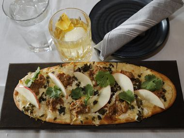Syracuse Fennel Sausage flatbread, topped with roasted hatch peppers, shaved apple and fontina cheese offered at The Stone House restaurant in Colleyville on Tuesday, October 20, 2020. The shareable is shown with the Stonefashioned cocktail, bulleit rye, stonehouse bitters, and charred orange over ice. (Stewart F. House/Special Contributor)