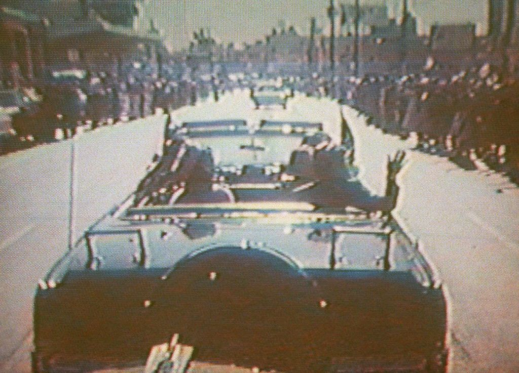 In this footage taken by presidential aide Dave Powers and photographed from a television screen, President John F. Kennedy, accompanied by his wife, Jacqueline, waves from his limousine in Dallas on Nov. 22, 1963.