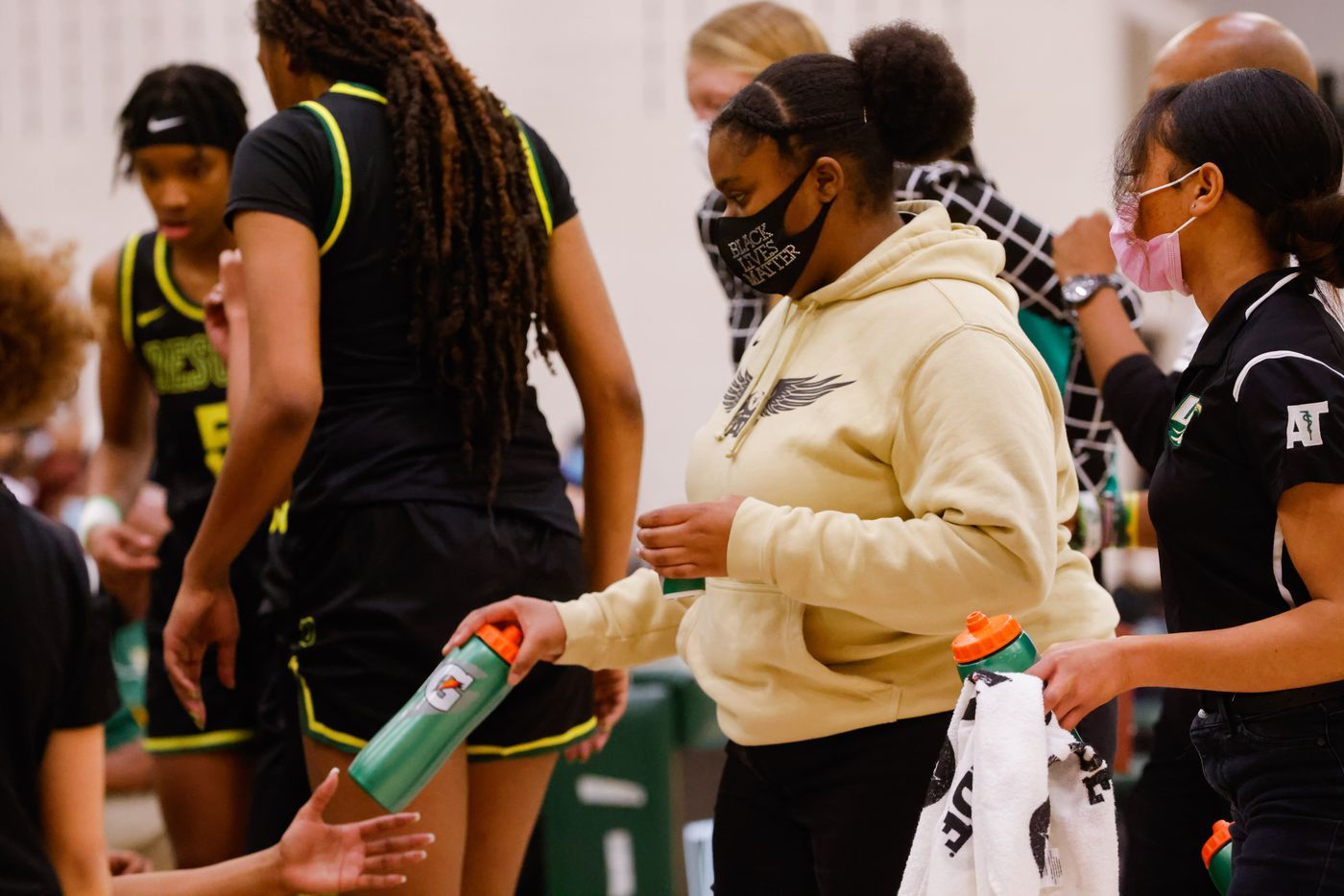 DeSoto's student trainers Corrie Crawford (Center) and Khiya Cockerham (right) give the players water during the second half of a girls basketball Class 6A Region II UIL game against Duncanville in Waxahachie on Tuesday, March 2, 2021. DeSoto won the game 52-39. (Juan Figueroa/ The Dallas Morning News)